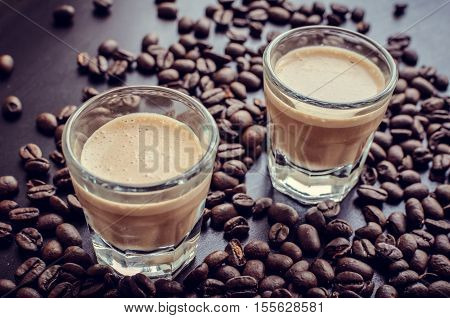 Espresso creamy liqueur served on table. Irish creme liqueur on dark background with coffee beans. Shot glass of creamy coffee liqueur with coffee beans. Alcoholic bavarage concept. Selective focus.