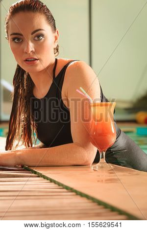 Attractive seductive woman in black dress relaxing at swimming pool edge poolside. Young sensual girl with tropical drink cocktail resting. Leisure.