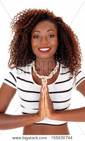 A lovely young African American woman folding her hands and prayiung isolated for white background.