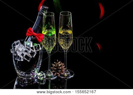 Bottle of champagne in an ice bucket with two wineglasses and pine cone