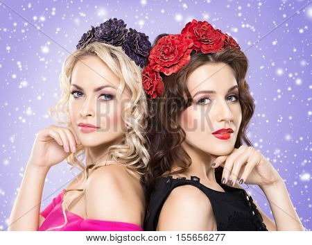 Beauty portrait of couple of attractive blond and brunette girls with curly hair and a beautiful headband over winter background. Christmas concept.