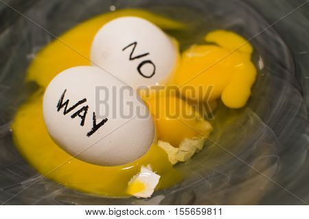 Nest eggs with words no way floating and sinking in a mess of yolks and broken eggs symbolic of change and challenge when eggs are in the wrong basket