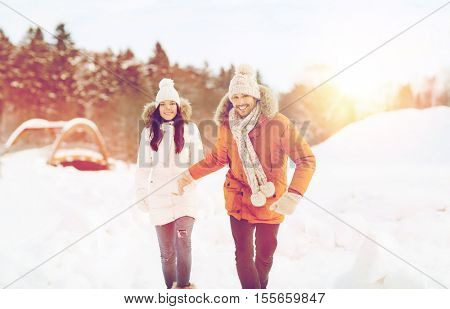 people, season, love and leisure concept - happy couple running over winter background