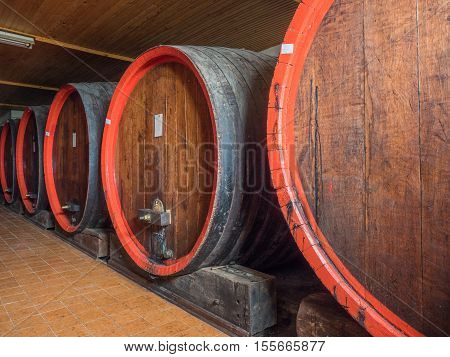 Picture of a brown wine barrels stacked in the old cellar of the winery. Background of the wooden barrels made of brown planking.