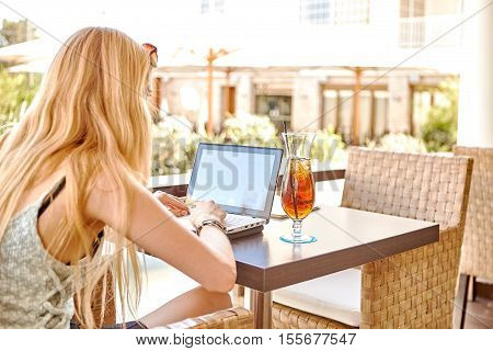 View of young smart female student learning on-line via laptop computer intelligent woman sitting in front open net-book with drink