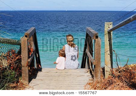 young charming mother and happy  daughter on the beach on the stairs leading to the beach