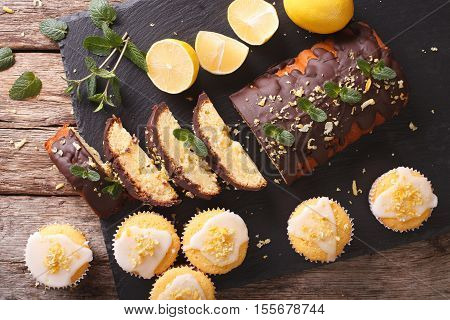 Sliced Lemon Cake With Chocolate And Lemon Muffins With Icing And Zest Close-up. Horizontal Top View
