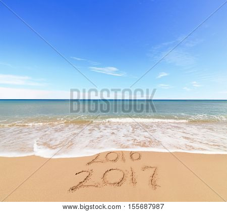 New Year 2017 is coming concept - inscription 2017 and 2016 on a beach sand the wave is covering digits 2016