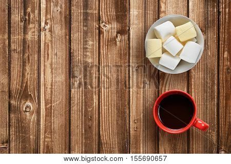 Marshmallow and coffee cup on wooden table top view