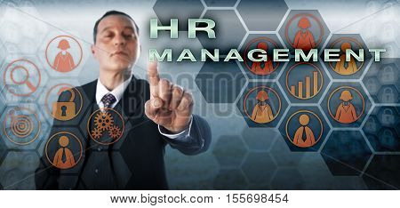 Human resources supervisor is touching HR MANAGEMENT on an interactive control monitor. Business metaphor for workforce planning recruitment training talent development and performance management.