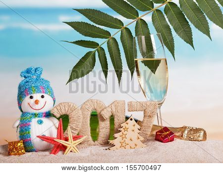 Figures 2017 champagne bottle and glass, snowman, leaf, Christmas tree, starfish, gifts in the sand against the sea.