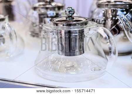 Glass teapot. Several kettles stand on a shelf.