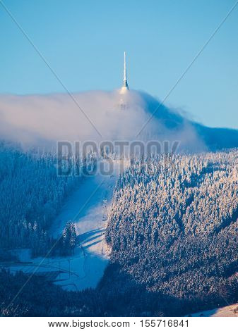 Jested transmitter and mountain hotel hidden in the clouds on sunny winter day with snowy ski slope, Liberec, Czech Republic