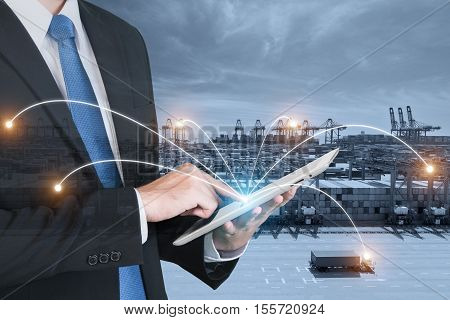 Double exposure of businessman hand holding digital tablet assistance control logistics system use for import export and logistics background