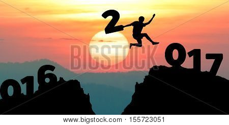 silhouette man jumps to make the word Happy New Year 2017 with sunrise. (New Year 2017 is coming concept.)