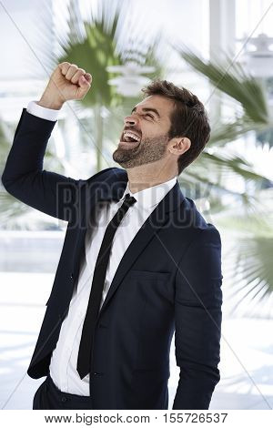 Businessman cheering his success in office with palmtrees