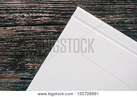 Hard cover on white glance cardboard book. Details on dark brown wood