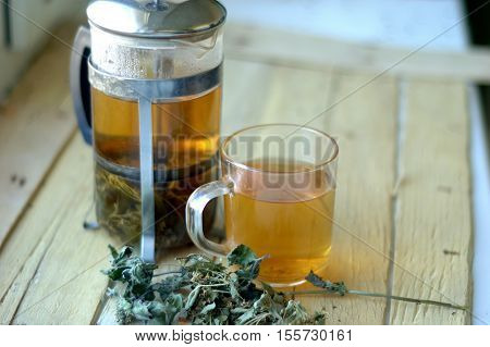 Green herbal tea in a teapot and cup on a wooden background.