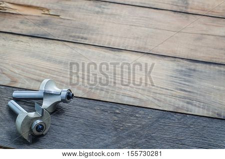 Woodworking tools milling cutters on a grunge background. Joiner's background. Carpenter tools on wooden table. Carpenter workplace top view.