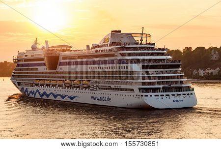 Hamburg, Germany - May 10, 2011: The AIDAluna cruise ship is leaving the harbor of Hamburg, Germany during dusk in beautiful sunlight with its passengers waving goodbye and enjoying the sight