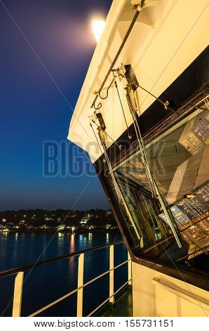 Hamburg, Germany - May 10, 2011: Cabin of a large contsiner ship at the Buchardkai Container Terminal in Hamburg at night with reflection of the containers loaded in the windscreen and Hamburg Blankenese in the background.