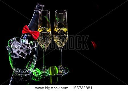 Bottle of champagne in an ice bucket with two wineglasses and mineral ball