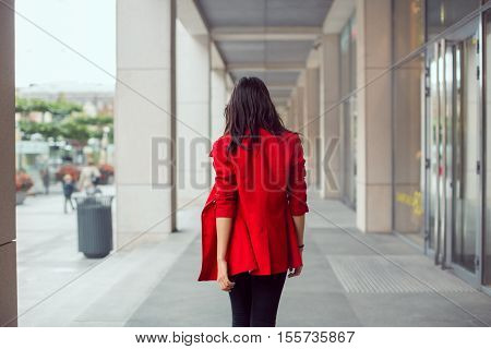 Rear view of asian woman walking outdoors in business casual red suite against city mall
