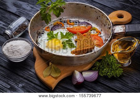 freshly made, delicious meal of eggs and vegetables on the black wooden table