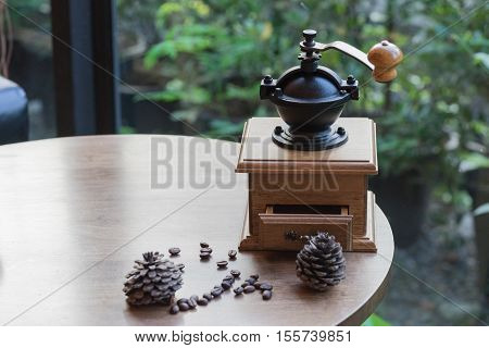 wooden traditional coffee maker with coffee seed on wooden table in coffee shop on natural view at relax coffee time / coffee maker and coffee seed