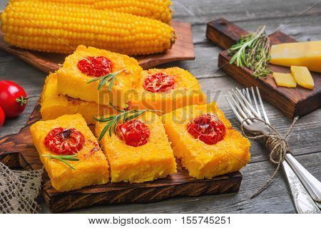 Pieces Corn polenta baked with cherry tomatoes Parmesan cheese on board. Boiled corn on wooden plate for polenta. Green for corn polenta thyme rosemary. Gray wooden background.