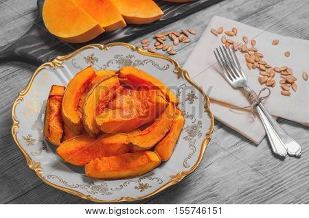 Halloween Baked pumpkin pieces on white vintage porcelain plate raw pumpkin pieces cut for baked napkin tissue pumpkin seeds on light white background wooden top view