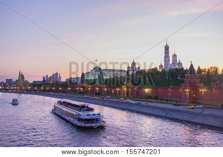 MOSCOW RUSSIA - MAY 10 2015: The twilight is the best time to make a trip along the Moskva river and enjoy the views of Kremlin in lights and other city landmarks on May 10 in Moscow.
