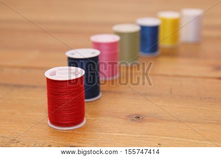 Row Of Multi-colored Cotton Reels Or Bobbins On A Wooden Sewing Table