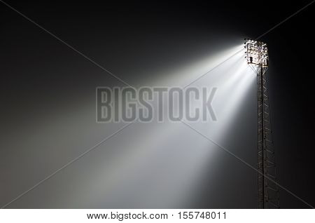 Sports ground stanchion flood lights lit up at night