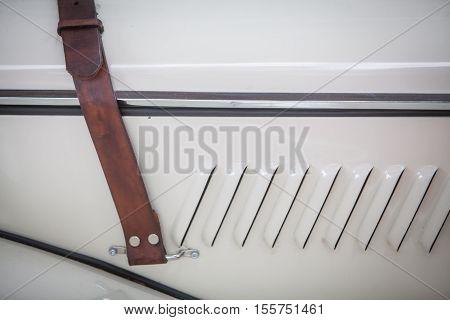 Close up shot of a leather belt on a vintage car's hood.