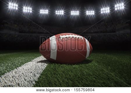 Low angle view of college style football on a yard line of a football field under stadium lights