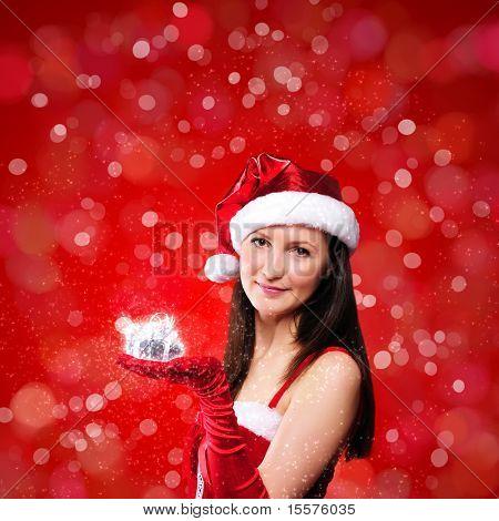 Retrato de una joven disfrazado de Santa Claus sobre un fondo rojo. Niña le da regalos. Feliz nuevo sí