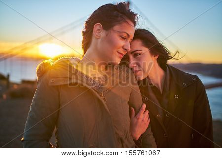 happy romantic lesbian couple with golden gate bridge in background with lens flare