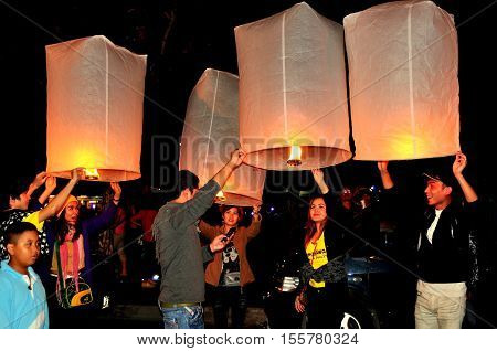 Chiang Mai Thailand - December 30 2012: Thais lighting paper lanterns to heaven for good luck on New Year's Eve near the Tha Phae Gate