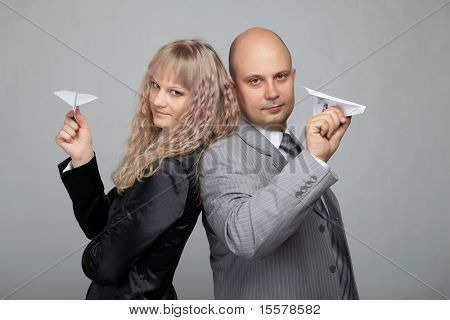 Funny business woman in a black suit and a bald businessman with a gray background run Aircraft