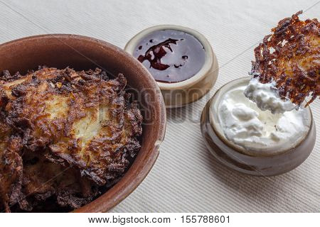 Latkes in a ceramic rustic brown bowl with sour cream and strawberry jam aside latkes with sour cream on it from side