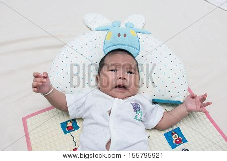 Cute baby newborn lying and crying on the bed