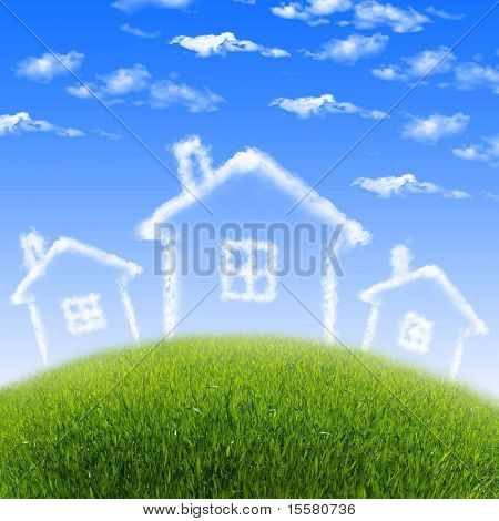 House of clouds in the blue sky against a background of green grass.