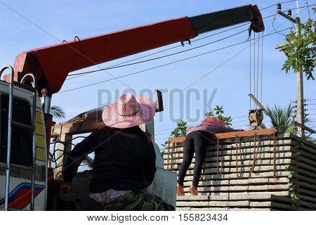 Worker controls of lifting crane in crane truck
