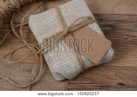 Closeup of a small fabric present with a blank gift tag on a wood table.