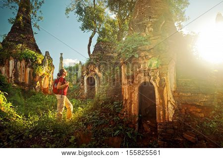 Backpacker traveling with backpack and looks at sunset ancient Buddhist stupa of the temple complex In Dein Inle Lake. Mayanmar Traveling along Birma freedom and active lifestyle concept