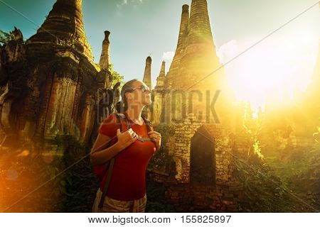 Woman backpacker traveling with backpack and looks at sunset between ancient Buddhist stupa of the temple complex In Dein Inle Lake. Mayanmar Traveling along Birma freedom and active lifestyle concept
