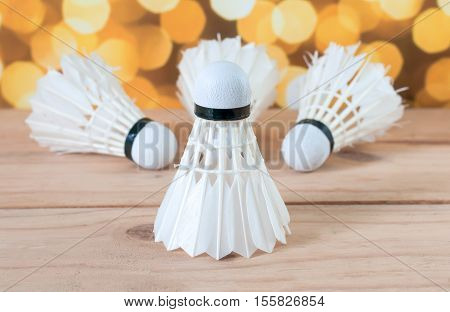 The Badminton White Shuttlecock On Wooden With Yellow Bokeh Lighting Background