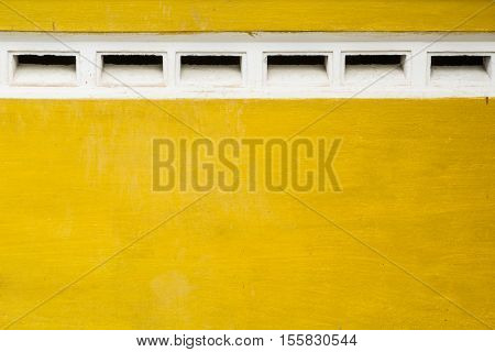 Yellow walls of an old building with vents white.