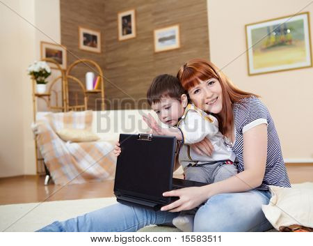 young mother working on a latop with her baby son